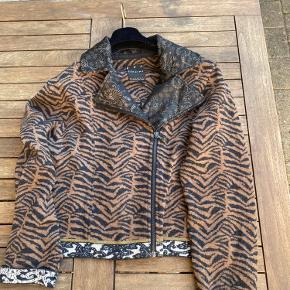 """Fantastisk smuk og meget luksuriøs kvalitets strik jakke/ trøje med en masse smukke detalje i mønster og vævning . Et dansk """"brand""""med en unik evne til at designe modetøj, der skaber nye standarder og rykker ved opfattelsen af trendy design. Varm jakke / trøje i ren uld  Bruges til hverdag og fest  Bryst mål ca 38-39 cm  Mål fra armhule til armhule 50cm"""