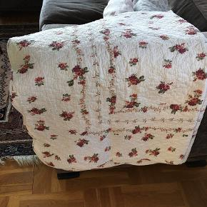 Vatteret sengetæppe / vattæppe / quilt. Offwhite med blomster. Tungekant. Bomuld. Længde 183 cm, bredde 137cm. Flot look. Pæn stand - dog et lille hul i stoffet på 1,5 cm. Se foto.  Vintage