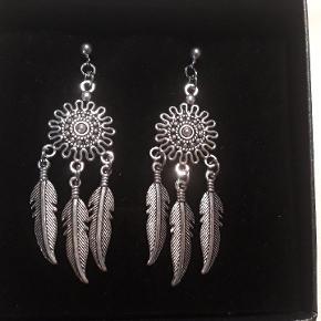Eget design. Øreringe i stål, de er 6.5 cm lange og 2 cm brede. Øreringene leveres i gaveæsker og kan sendes for 20 kr med Post Nord, almenlig brev.