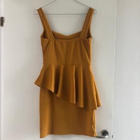 Flot karrygul kjole med flot udskæring og peplum. Aldrig brugt. Størrelse S. Sælges da købt for stor (jeg er en xs).