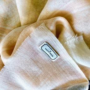 Lækkert let tørklæde i partisanmønster i fersken/cremhvid med fine frynser. 100% uld. Størrelse: ca. 130x130 cm