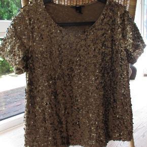 Guldpalliet bluse fra H&M i str M. Er i 2 lag og det inderste lag er blød polyester.  Hel længde: Ca. 59 cm BM Ca 2 x 50 cm.  Se også mine over 100 andre annoncer med bla. dame-herre-børneog fodtøj