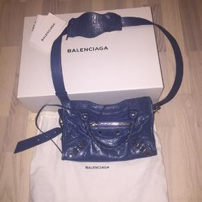 """Overvejer at sælge min enormt flotte og velholdte Balenciaga taske. Tasken er i Modellen classic City bag og størrelsen """"mini"""".  Tasken er købt i Illum for nogle år tilbage og sælges da jeg ikke får den brugt nok:(   Som det ses på billede 2 og 3 har den slid ved dens kanter (intet fremtrædende og tydeligt slid og slid der ikke kan undgåes at komme efter brug). Derudover er der intet slid på tasken.   Til tasken medfølger alt. Herunder bl.a. boks, dustbag og bon.   Skriv gerne for flere billeder:)"""