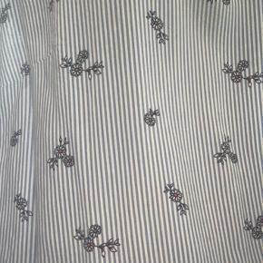Fin stribet bluse med detaljer i bunden af blusen og små blomster. Den er str.42, men på ingen måde tilsvarende størrelsen. Vil mene den passer en 36/38 eller s/m