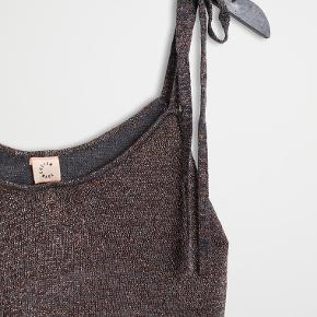 Fin strik-top fra Custommade i uldblanding med sølvtråde. Justerbare stroppe, der bindes efter ønske. Aldrig brugt.
