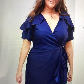 Wrap kjole med bindebånd, hvilket gør den lidt mere fleksibel i størrelsen Brystmål: 128 cm Taljemål: 116 cm