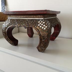 Virkelig smukt lille bord af træ med de flotteste udskæringer og dekoration med sten og spejle. Det skulle stamme fra Bali. Mål cm h:28,5 b:35,5 l:35,5 Kan sende flere billeder