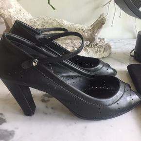 Smukke Chanel heels i perforeret sort skind med peep-toe og ankelrem med sølv CC logo-knap. Brugt max 5 gange - der er sat såler under forsål. Str 42 som svarer bedst til Dk str 40-41 da Chanel sko sizer småt. Kommer i original Dustbag.