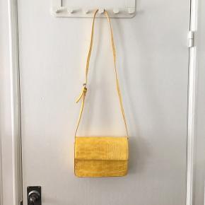 Gul cross-over taske i krokodille-look, med justerbar rem 🌼 Brugt få gange og fremstår derfor næsten som ny. Kan afhentes i Aarhus C eller sendes mod betaling af porto 📦📮