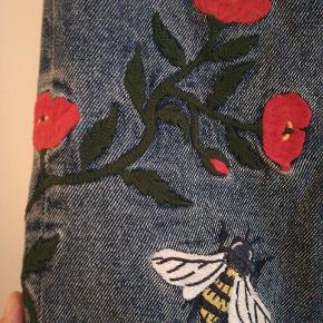 High relaxed denimjeans str. 27 med blomster broderier ned af siden og en bi på den ene baglomme. Desværre er de for små til mig. Beklager de er lidt krøllede på billederne