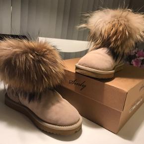 Korte bamsestøvler med ægte pels.  Støvlen er lavet i ruskind, med pels fra en vaskebjørn og uld for indeni.  Støvlen er kun brugt ganske lidt og fremstår som nye.  ⭐️jeg sender gerne, og ellers kan det afhentes i Farum eller i Fields (Amager) ⭐️