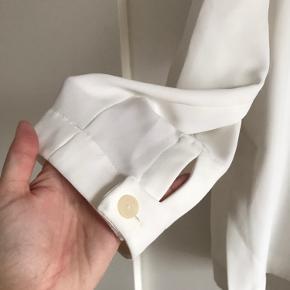 Fineste skjorte/blazer/bluse i let oversize pasform. Lukkes med en knap og kan bindes i siden. Har løse ærmer med fin detalje og knappe-lukning samt slids i hver side. 100% polyester.