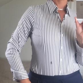 H&M skjorte billede 1: 50 kr. pp.og gebyr. Jeg har den samme skjorte som på billede 1 til salg i helt lys gul også. Samme model, størrelse og pris. Hedder L, svarer til 40-42.  Str. 42.: Jeg sælger rigtig mange skjorter og bluser i gode mærker og rigtig flot stand (18 stk). Nogle er nye og ubrugte, nogle er som nye, nogle er gmb. Mærkerne er både dyre mærker som Replay, Seidensticker, Desigual, Made by Andersen og Gervig og 'lækre dagligmærker' som Vila, Saint Tropez, Trusca, Dranella og Vero Moda og så to kortærmede fra H&M - de to koster så kun 50kr stk. og det samme gør de to ultratynde bomuldstoppe fra Trusca (råhvid og rosa). De er nye.  Det er flere annoncer for at få plads til alle fotos. Jeg måler ikke. Men til sammenligning er jeg 180 høj og bruger str 42 i bluse, men 44 hvis det er tætsiddende (bh 70I). Og jeg passer alle skjorter og bluser der er vist undtagen de tre taljerede.