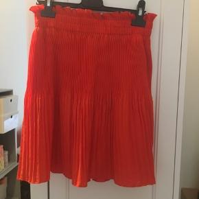 Flot nederdel i god stand. Det er en str. 38, men passer også 36, da der er stretch i, måske endda også en str. 40.  Farven er rød orange, men det var lidt svært at fange på billederne, da den er mere orange i virkeligheden. Kan afhentes på Østerbro eller sendes med DAO.