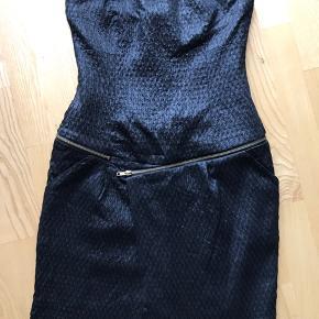 Stropløs kjole i skinnende sort stof - fin detalje med lynlås-bælte samt lommer i siderne.