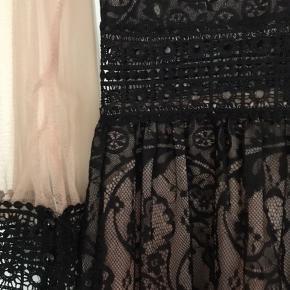 Skøn kjole med sort tyk blonde og gennemsigtig naturfarvet stof. Jeg har købt den i Italien og er en lille L. Den sidder mega godt. Har selv brugt den til en nytårsaften - smuk med en sort høj hæl 👍🏻.  Se også alle mine andre annoncer 💃💃  Byd!