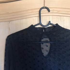 Gennemsigtig bluse fra Vila med prikler og høj hals med to lukkeknapper bagi.  Rigtig fin under en strik og med en blonde Bh indenunder.  Mærket er klippet ud, så det ikke så træls ud.