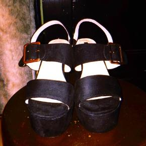 Sorte platform sandaler/hæle. Materialet er tekstil og minder om imiteret ruskind.  -Brugt indedørs 3 gange