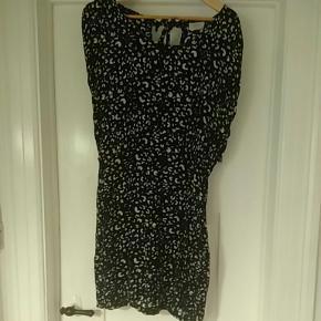 Kjolen har lynlås i siden og elastik i taljen, så den sidder til. Kjolen bindes i nakken.