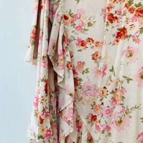 Skønneste slå-om nederdel fra Lollys Laundry. Floral skirt er en slå-om nederdel og har fine asymesriske flæserkanter.  Aldrigt brugt dog uden mærker  Længe: 98 Waist: 40 x 2 ( slå-om så passer også m)