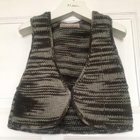 Fin grå vest fra Rabens Saloner i 100% uld. Str hedder M/L, men tjek gerne mål for en sikkerhedsskyld. Brystmål: 42 cm på tværs+stretch dvs 84 cm i omkreds + stretch. Længde: 40 cm fra nakken og ned. Lukkes med en hægte foran. Søgeord: strikket vest uld top strik stribet grå knit stripes striber grey