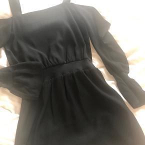 Smuk off-shoulder kjole i sort med ærmer fra Designers Remix. Størrelse 36. Aldrig brugt og står derfor som ny.