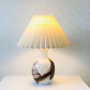 """Sjælden og flot Cascade bordlampe fra Holmegaard, designet ca. 1970 af Per Lütken (1916-1998). Lampe i opalglas med farvede flusser, der under bearbejdning smelter og danner uforudsigelige mønstre. Overfang i krystalglas. Cascade blev formgivet som en reaktion på det """"perfekte"""" ensartede glas, men var for dyrt og besværligt til en stor produktion. Ses ikke ofte. Højde med fatning: 39 cm Højde til fatning: 33 cm Diameter: 19 cm Vægt: 2843 g Signeret: Nej Prisen er excl. skærm"""