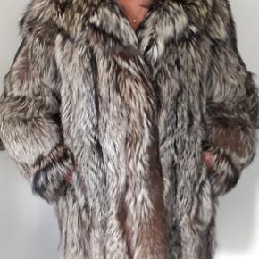 """Dejlig, vamset og varm pelsjakke i ægte sølvræv.   Den ser lidt pjusket ud, fordi den har været opbevaret i en papkasse med sæbe i 2020 (= for at undgå utøj) Ellers har den altid været til pelsopbevaring om sommeren.  Og den blev renset i efteråret 2019, og er brugt ca. 2 gange efter det.  Den skal hænges op, og børstes med en blød børste.  Pelsen er syet til mig af Bundtmager Præst i holbæk.  Desværre """"fælder"""" den (=de lyse hår knækker af) - Det er grunden til, at den sælges så billigt. Det ses tydeligst der, hvor man har rørt den hele tiden: f.eks ved hægterne og ved kraven, hvor der sidder en elastik, der lukker kraven.  Jeg vil tro, at den kan holde sig pæn i 3-5 år før mange af de lyse hår er knækket af, men den kan nok stadig bruges efterfølgende.   Det er en billig måde, at få en stadig flot pels for ca. 250 kr. om året.  Efter en årrække vil den nok se ud som det sidste billede. det er ved hægterne foran (lidt a la bjørneskind).   Pelsens mål: Længde 88-90 cm. + krave ca. 15 cm. Ærme 69-70 cm.  Modellen er 170 cm. Og en str. 46  Grunden til, at jeg sælger den er, at jeg sidder i kørestol. Og det er svært at proppe en vamset pelsjakke ind i sådan en..."""