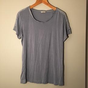 T-shirt med flotte silkedetaljer ved ærmerne. Den er en støvet blå.
