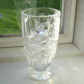 Vase, Krystalvase, Polsk krystal  Som ny. Har kun stået til pynt og ikke været brugt som vase  En rigtig super flot og stor krystalvase der er helt uden skår, ridser, .og misfarvninger  Den glinser og ståler fantastisk flot med alle den slibninger når den rammes af solens stråler  Vasen er i Polsk krystal og er fra 1980 erne  Vasen er ca. 23 cm høj og ca. 12 cm i diameter  Vasen er tung og vejer 1968 g så den står godt og vælter ikke så let  Sender gerne hvis køber betaler fragt 33 kr sendt  med forsikret forsendelse