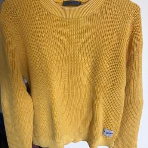 Super fed strik fra Calvin Klein Jeans. Kun brugt ganske få gange og derfor ingen brugsspor. 100 % bomuld. Farven er vasket gul, som giver den et mere råt udtryk.