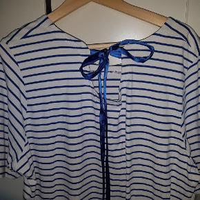 """Dejlig kjole i ren bomuld. Brugt 5-6 gange, men i pæn stand. Fin detalje med bånd og """"kighul"""" i nakken. Der skal lige sys et par sting hvor båndet i nakken er fæstnet, men det er alt.  Bryst ca.: 2 x 60 cm, længde ca. 94 cm.  JEG BETALER FORSENDELSEN MED DAO!  Frisk, stribet kjole Farve: Hvid/blå"""