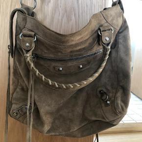 Varetype: Velo Størrelse: Velo Farve: Brun  Balenciaga taske model Velo i brun ruskind. Tasken er i fin stand. Er lidt mørkere på hankene, men ikke meget. Hjørner på bagside er også lidt mørkere, men ikke slidte.