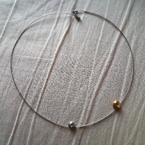 En sølv halskæde, med et guld og sølv vedhæng.