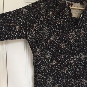 Løs skjorte med lang skulder. Mønster er coral, grangrøn og off white. 1/2 brystvidde 64 cm Længde fra skulder 65 cm Skulder 26 cm og ærme længde 47 cm