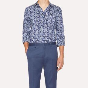 Varetype: Skjorte Farve: blå Oprindelig købspris: 1600 kr.  Paul Smith skjorte med fedt blomster print og lærke detaljer, stadig aktuel i butikkerne. Lavet i ren bomuld.  Første billeder er modelbilleder  MP 500