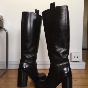 Langskaftede støvler af robust kvalitet. Tårnhøje (11 cm!), brede hæle. Af det belgiske modehus A. F. Vandevorst. Købt til nypris i A Pair i København K ved Kongens Nytorv til  5400,-. Jeg har haft dem på (kortvarigt) to gange, men har sat dem som 'ny, med prismærke', da de fremstår som nye uden brugsspor overhovedet samt i perfekt stand. Og der er stadig prismærke på. Samt original-æske medfølger. Man er velkommen til at prøve på før evt køb  Denne vare sendes ikke  Mp: 2200,-