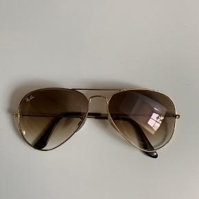 Solbriller i guld fra RayBan med brunlige glas. Modellen hedder: RB 3025 AVIATOR LARGE METAL. Etui og pudseklud medfølger.