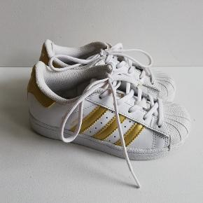 Adidas Superstar sneakers i Str. 28 hvid/guld  Indvendigt mål: 17,5 cm Brugt 2 gange - flot stand  Pris: 200,- plus porto  Fast pris (nypris 500kr) Sender med DAO