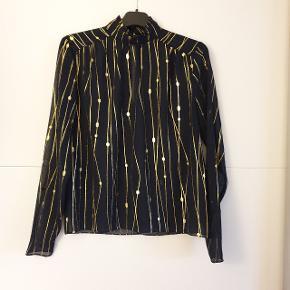 Bluse fra MbyM, navy med guldprint, let gennemsigtig, turttleneck med en lille flæse foroven, udskæring i nakken som lukkes med knapper. Brugt en enkelt gang.  Prisen er ekskl. forsendelse.