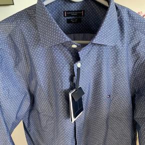 Super flot skjorte fra Tommy Hilfiger Tailored. Skjorten har ikke været brugt og den svare til str 42 i skjorte størrelse og ellers str L.