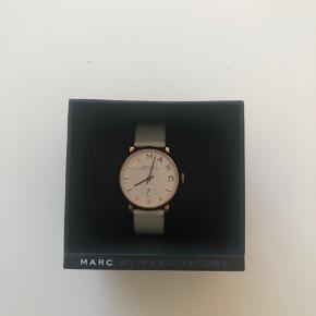 Marc Jacobs ur med hvid rem og rosaguld urskive. Der er en mindre ridse i glasset, og som vist på billedet er remmen en anelse misfarvet. Desuden skal det have nyt batteri.