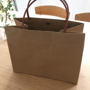 Skuldertaske i 'paper bag' look, lavet af behandlet papir og med læder hanke.   Format 30x38 cm (ekskl hanke)  Ubrugt.   350,-