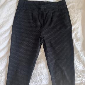 Nålestribede. Falske lommer bagpå. Snørre og mulighed for bælte. Stumpede bukseben.