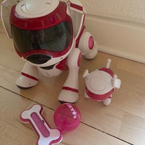 Det er en elektronisk hund med udstyr til som en lille hund ved siden af, en godbid og en lille bold. Den kan hoppe og alt mulig.
