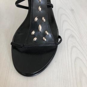 Flotte sorte stiletter fra Franco Banetti (replica) med fine nitter foran.  Der er elastik i den øverste rem.  Sålen indvendig måler 25,5 cm.  Selve hælen måler 8 cm.  Aldrig brugt.