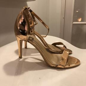 Super flotte heels med 8,5 cm hæl.  De er brugt en enkelt gang og har fået et hak bagpå Venstre hæl. Hakket er IKKE gået gennem guldet