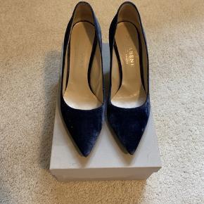 Sælger mine smukke stilletter, da mine fusser er for store. De er i en flot blå velour og ca. 7 cm høj hæl. Normal str. 38. Nypris; 1500,- original æske følger med.