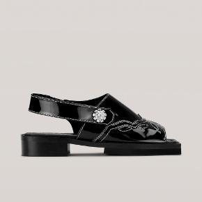 """Flotteste sandaler fra GANNI i sort lak med deres """"berømte"""" jewel button.  Str. 40.  Aldrig brugt. Udsolgt på hjemmesiden.  Æsken haves desværre ikke længere.   Handels via trendsales og sendes med dao på købers regning."""