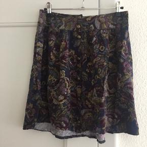 Blomstret a-formet nederdel med høj talje. Lukkes med metalknapper hele vejen ned foran. Måler 36 (x2) cm i taljen og er ca. 45 cm lang. Størrelse M